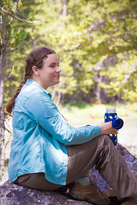 Kaitlin Lubetkin, wearing a turquoise jacket, brown pants, and brown hiking boots, poses atop a rock with trees in the distance behind her.