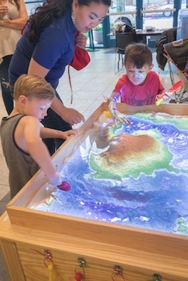 Two children and a woman at the augmented-reality sandbox.
